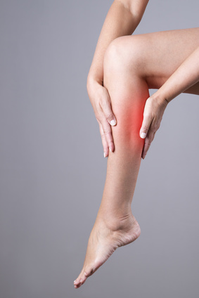 Pain in the calf muscle of the woman. Massage of female feet. Pain in the human body on a gray background with red dot
